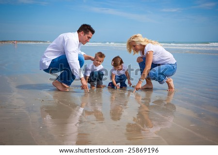 Family on a beach looking at findings in the sand - stock photo