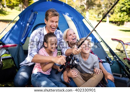 Family on a camping trip fishing outside their tent - stock photo