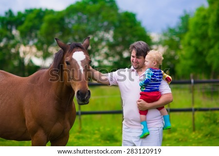 Family on a farm in summer. Father and baby son feed a horse. Outdoor fun for parents and children. Kids playing with pets. Child feeding an animal. Dad and little boy play together in the garden. - stock photo