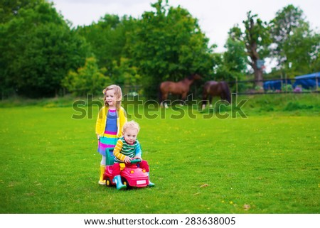 Family on a horse farm in summer. Brother and sister riding a toy car. Outdoor fun for children. Kids playing with pets. Child feeding an animal. Girl and little boy play together in the garden. - stock photo