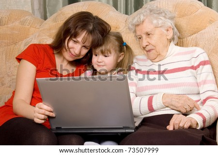 Family on a sofa with the computer - stock photo