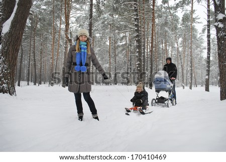 Family on a walk in a winter snow-covered lesu.Mama lucky son sledging father carries the stroller. - stock photo