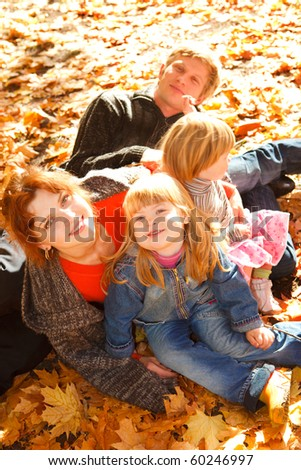 Family on autumn leaves - stock photo