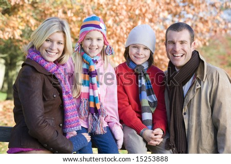 Family on autumn walk sitting on fence - stock photo