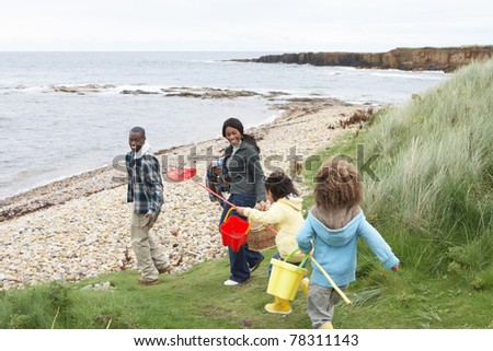Family on beach collecting shells - stock photo
