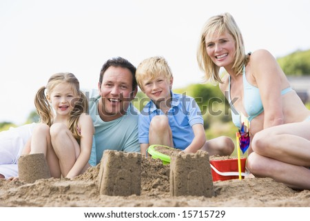 Family on beach making sand castles smiling - stock photo