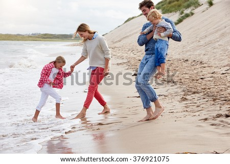 Family On Beach Vacation Playing By Sea - stock photo