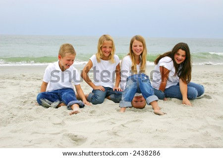 Family on beach with silly baby - stock photo