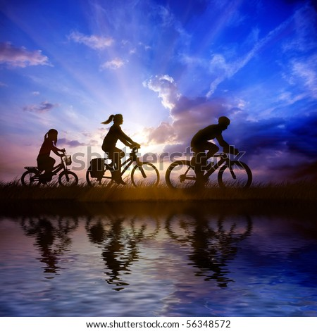 Family on bicycle ride at sunset - stock photo