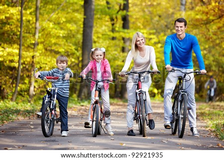 Family on bikes in the park in autumn - stock photo