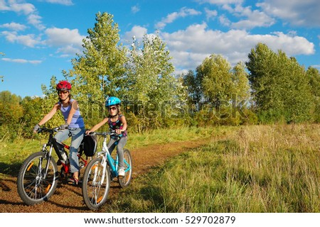 Family on bikes outdoors, active mother and kid cycling, fitness and healthy lifestyle concept