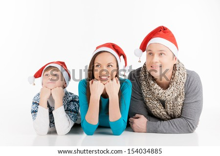 Family on Christmas. Cheerful family in Santa hats looking away and smiling while isolated on white - stock photo