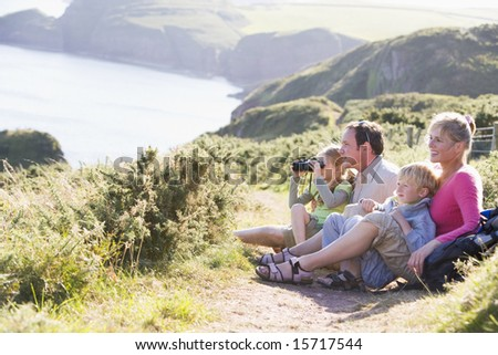 Family on cliffside path using binoculars and smiling - stock photo