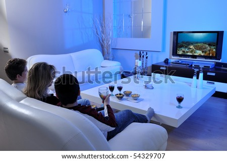 Family on couch watching TV - stock photo