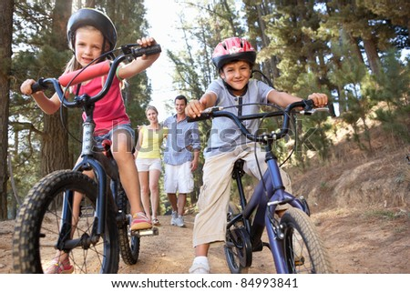 Family on country walk with bikes - stock photo
