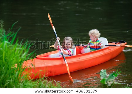 Family on kayak and canoe tour. Two little kids paddling in kayaks in a river on a sunny day. Children in summer sport camp. Active preschoolers kayaking in a lake. Water fun during school vacation. - stock photo