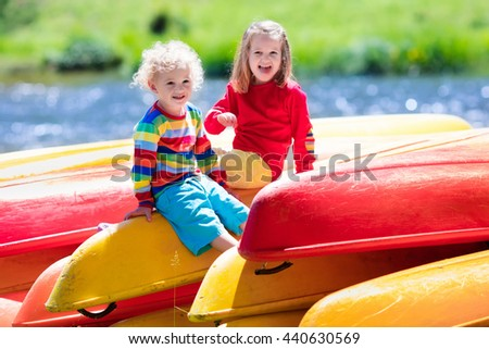 Family on kayak tour. Two kids sitting on pile of kayaks at a river shore on a sunny day. Children in summer sport camp. Active preschoolers kayaking in a lake. Water fun during school vacation. - stock photo