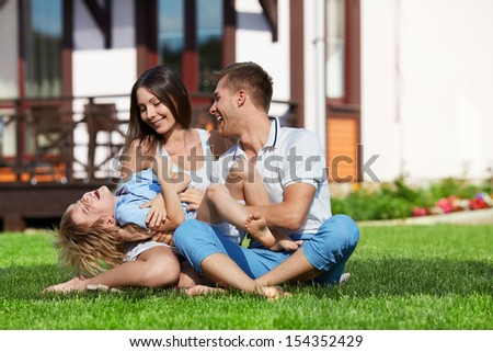Family on lawn at home - stock photo