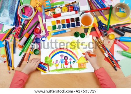 family on meadow with rainbow and house child drawing, top view hands with pencil painting picture on paper, artwork workplace - stock photo
