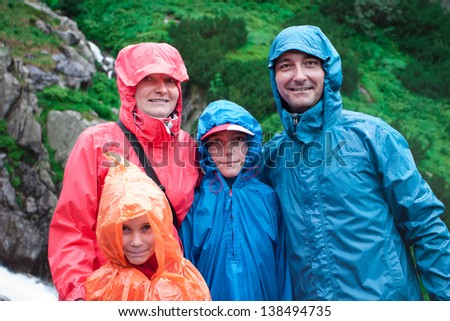Family on mountain trail on a rainy day. Green slope in background - stock photo
