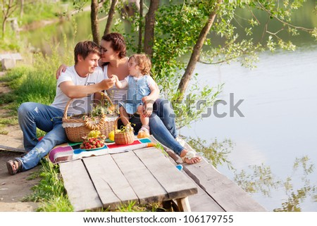 Family on picnic near the lake - stock photo