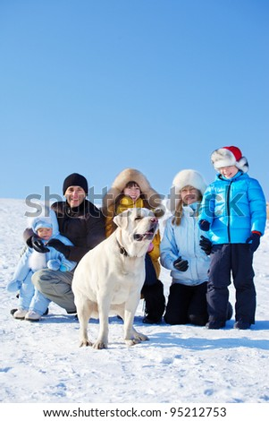 Family on snow and Labrador dog in front - stock photo