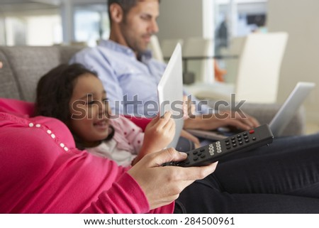 Family On Sofa With Laptop And Digital Tablet Watching TV - stock photo