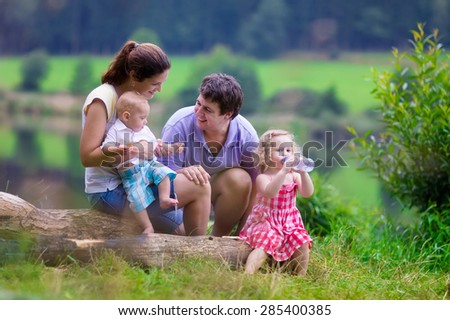 Family on summer hike. Young parents with kids hiking next to a lake. Mother, father and two children having picnic outdoors. Active trekking with baby and toddler. Beautiful nature of Germany. - stock photo