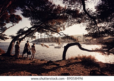 family on the beach at sunset. - stock photo
