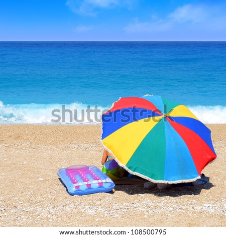 Family on the beach behind the sunshade - stock photo