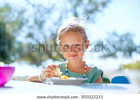 family on the beach having breakfast in sunny day - stock photo
