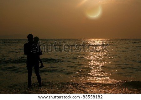 Family on the beach looking on sunset