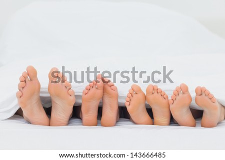Family on the bed showing their barefoot - stock photo