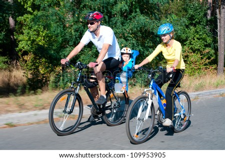 Family on the bikes in the sunny forest.Shot with low shutter speed to achieve motion blur - stock photo