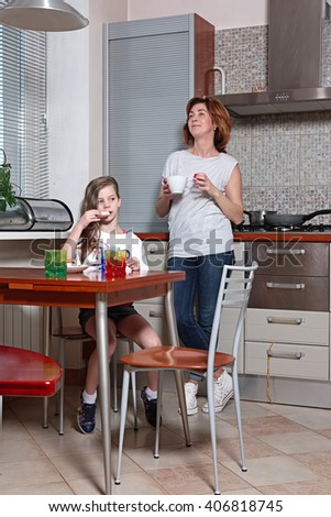 family on the kitchen behind the table drinking beverage and eating sweets - stock photo