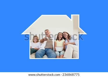 Family on the sofa watching tv against blue vignette