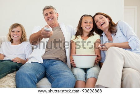 Family on the sofa watching tv together - stock photo