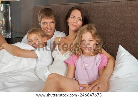Family on vacation in a hotel room bed  - stock photo