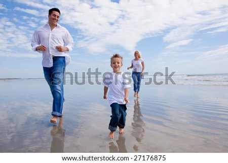 Family on vacation running on the beach - stock photo