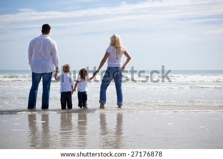 Family on vacation standing at the ocean, looking ahead - stock photo