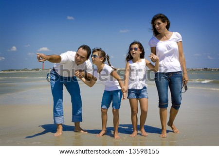 Family on vacation walking on a beach - stock photo