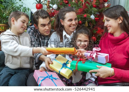 Family Opening Christmas Gifts At Home In Front Of Christmas Tree