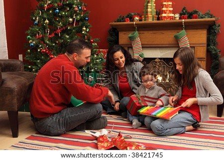 Family opening presents by Christmas tree - stock photo