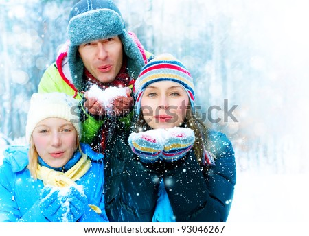 Family Outdoors.Happy Family with kid blowing Snow.Winter - stock photo