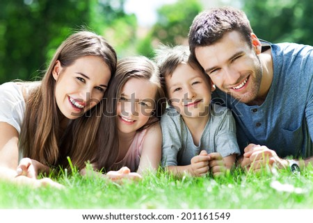 Family outdoors lying on grass - stock photo