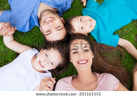 Family outdoors lying on grass