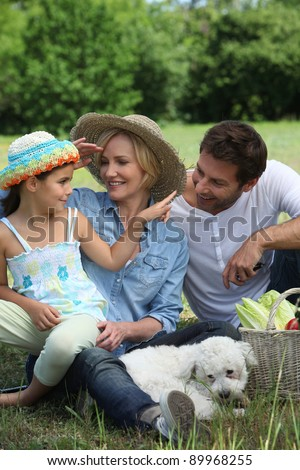 Family outdoors with their dog - stock photo