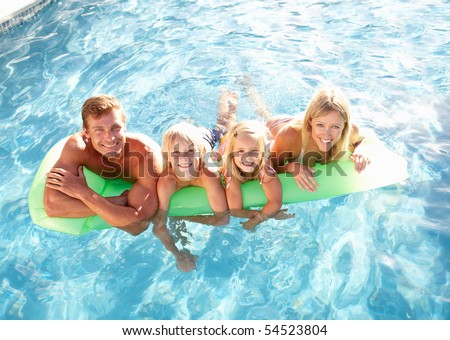 Family Outside Relaxing In Swimming Pool - stock photo