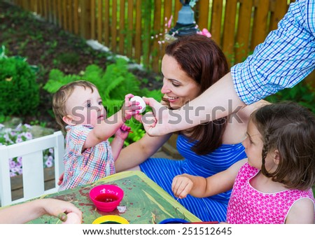 Family painting and decorating Easter eggs outside during the spring season in a garden setting.  Mother smiles at her boy as he reaches for a new egg from his father to color dye. Part of a series.  - stock photo