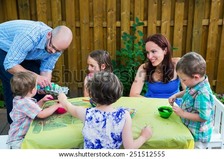 Family painting and decorating eggs outside during the spring season in a garden setting.  Mother and father with children together color dyeing Easter eggs.  Part of a series.   - stock photo